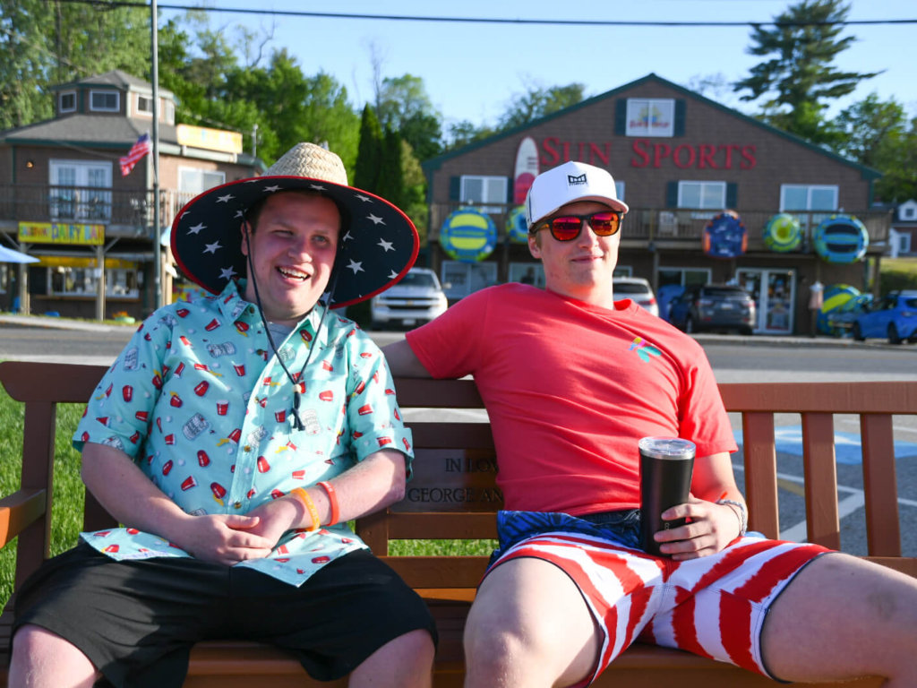 Two of our friends sitting down on a bench outside sunsports soaking up the sunshine