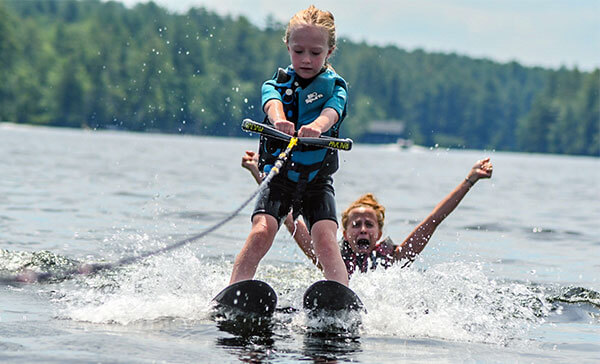 Our young skier friend Maddie learns how to waterski for the first time while her mom cheers in the background.