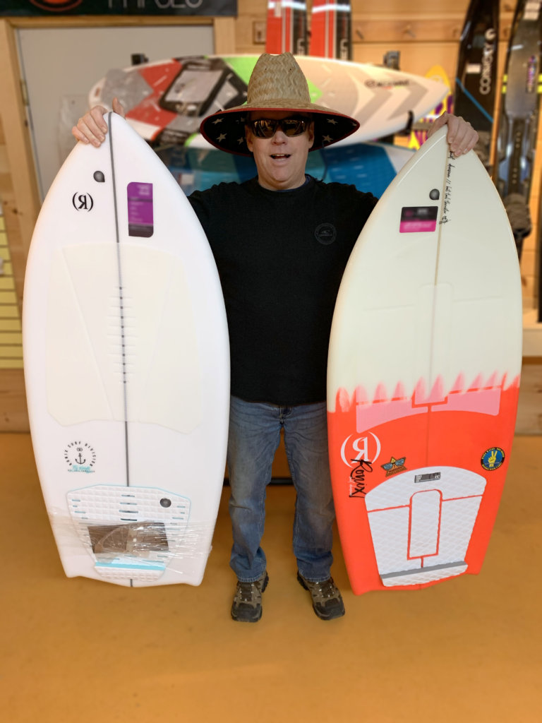 Sun Sports+ famous Wake Wizard stands holding two of Ronix's Wakesurf boards: The Mens and Women's Bat Tail Thrusters